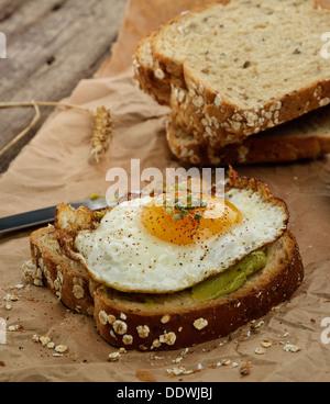 Avocado Breakfast Sandwich With Fried Egg - Stock Photo
