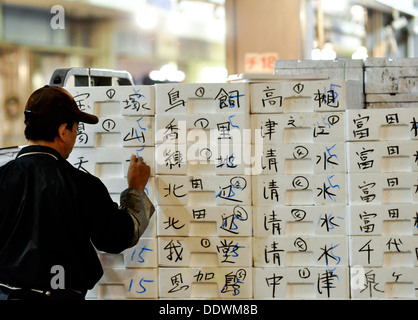 Worker at Osaka's Municipal Central Wholesale Market writing on boxes of sold fish and other seafood. - Stock Photo