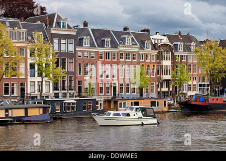Amsterdam river view, houses and houseboats on the Amstel river in Netherlands, North Holland province. - Stock Photo