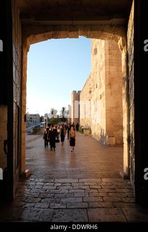 Ultra orthodox Jews entering the stone portal of Jaffa Gate or Bab al-Khalil one of eight gates of the Ottoman walls - Stock Photo