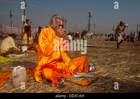 Naga Sadhu Portrait - The Great Renounce covered with beads, wooden ash and tilak on his forehead at Kumbh Mela - Stock Photo