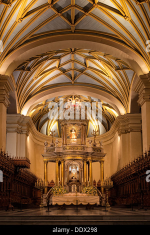 Catedral of Lima: gilded altar seen from front, with graceful gilded ribbed arched ceiling, wooden roccoco choir - Stock Photo