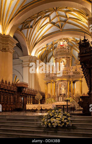 Catedral of Lima: gilded altar seen from side, with graceful gilded ribbed arched ceiling, wooden rococo choir stalls - Stock Photo