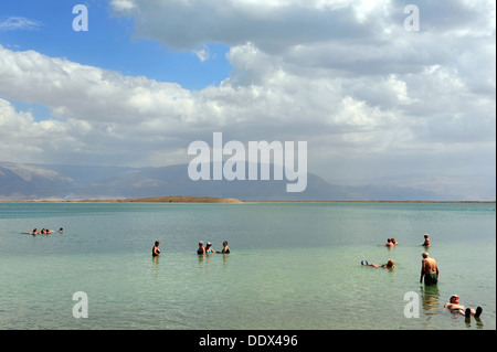 People floating over the dead sea in Israel - Stock Photo