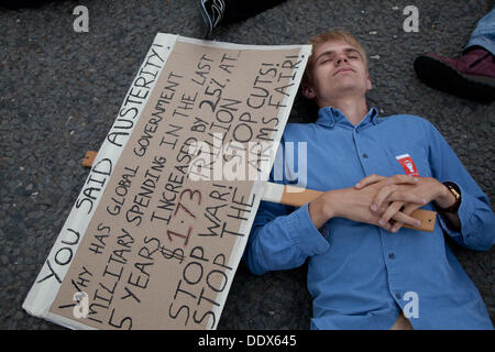 London, UK. 8th Sep, 2013.  Anti arms protestors hold a 'die in' outside one of the entrances to the Excel center - Stock Photo