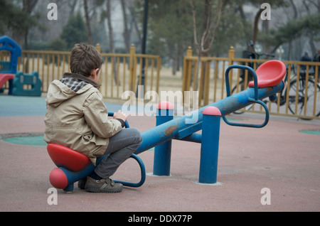 A small boy sitting alone on a seasaw at an empty playground - Stock Photo