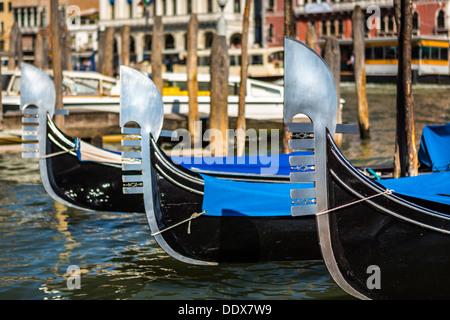 Three venetian gondolas moored on a water street in Venice, Italy - Stock Photo