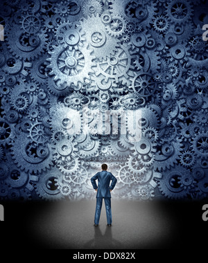 Business leadership training concept as a businessman facing a huge human head made from gears and cog wheels connected - Stock Photo