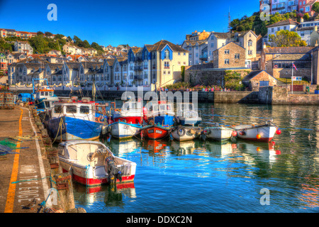Fishing boats with bright colours Brixham harbour Devon with houses on hillside in background in HDR - Stock Photo