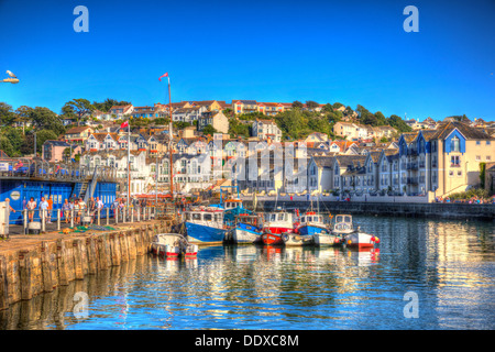 Brightly coloured boats Brixham harbour Devon with houses on hillside in background in HDR - Stock Photo