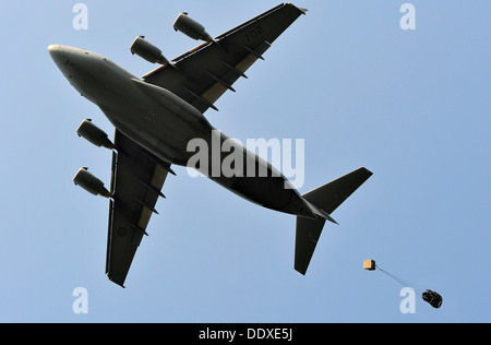 A Royal Canadian Air Force C-17 Globemaster III cargo aircraft drops a payload by parachute over a drop zone August - Stock Photo