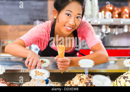 Young Asian saleswoman in an ice cream parlor takes a scoop of ice cream - Stock Photo