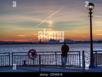 Man looking over to Birkenhead-Belfast Stena line ferry, from Albert Dock at Nighttime liverpool Merseyside England - Stock Photo