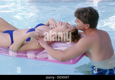 couple relaxing in a pool - Stock Photo