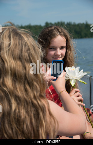 Girl taking a picture of her friend, Lake of The Woods, Keewatin, Ontario, Canada - Stock Photo