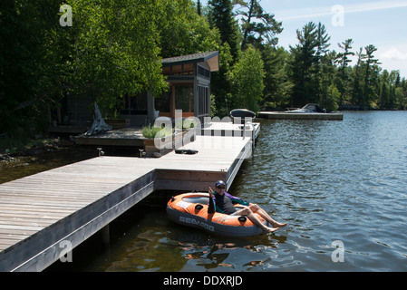 Man sitting on an inflatable raft floating in a lake, Lake of The Woods, Ontario, Canada - Stock Photo