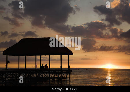 Man and woman sitting on the end of a wooden pier at sunset over the Indian Ocean Mauritius - Stock Photo