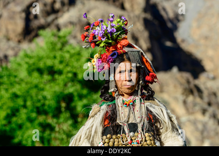 Woman of the Brokpa tribe wearing traditional dress with flower headdress - Stock Photo