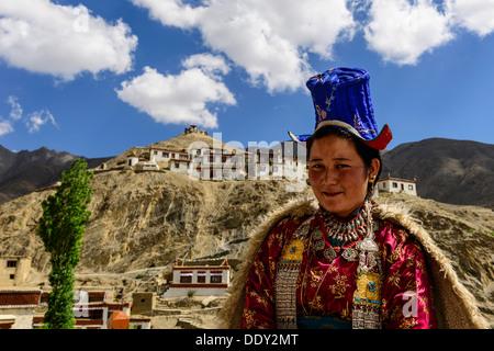 Ladakhi woman wearing traditional dress, Lamayuru Gompa at back - Stock Photo