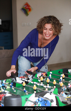 Young woman plays foosball (Table football)  - Stock Photo