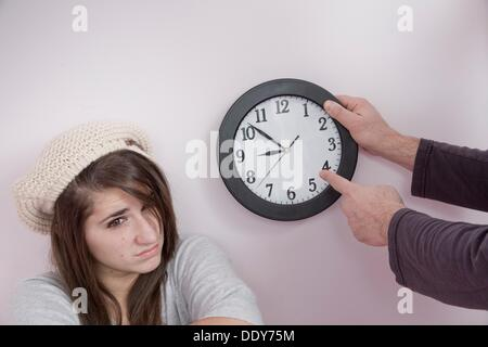 Father pointing to a clock next to his teen daughter - Stock Photo