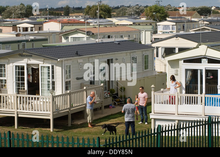 Static caravan holiday homes chalets, permanent camp site St Osyth Essex UK. Families family chatting  St Osyth - Stock Photo