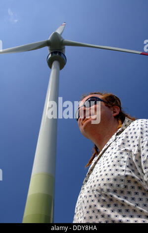 Dennis Stanley, wind turbine engineer, with Enercon wind turbine in background. - Stock Photo