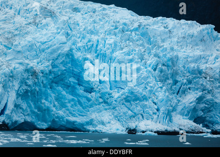 Close-up of Alaskan blue glacier edge and ocean dotted with ice chunks from glacial calving - Stock Photo
