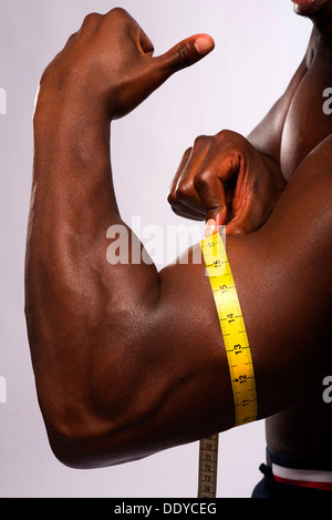 Man measuring his biceps with a tape measure - Stock Photo