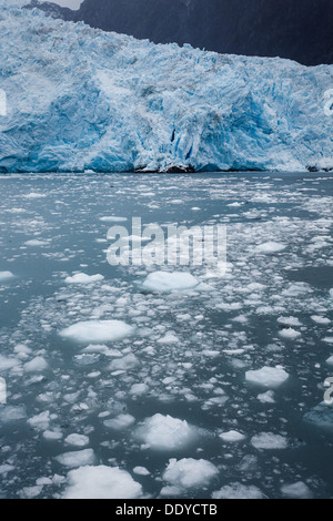 Close-up of the edge of a blue glacier and calving ice or ablation floating in the Alaskan ocean waters - Stock Photo