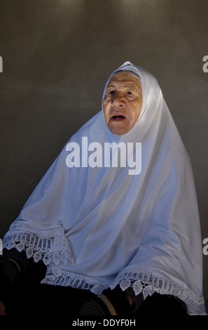An elderly Palestinian woman wearing a traditional al Amira headdress in the West Bank Israel - Stock Photo