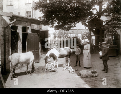 Horses and a dog in a stable yard in the centre of Landskrona, Sweden, 1912. The owner, his wife and their sons - Stock Photo
