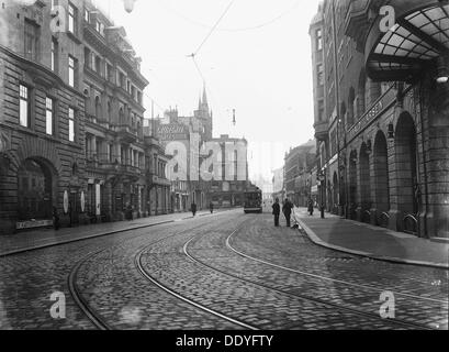Tram on a street in Malmö, Sweden, c1920. A street cleaner talking with a man. From the Malmo Museum Collection. - Stock Photo