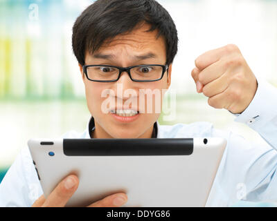 Young businessman, Asian, with glasses, iPad, hand clenched in a fist, upset, angry, stressed out - Stock Photo