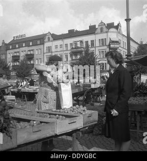 Woman buying potatoes from a fruit and vegetable stall in the market, Malmö, Sweden, 1947. Artist: Otto Ohm - Stock Photo