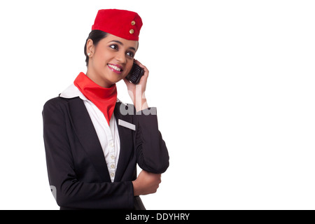 Happy young airhostess on call isolated over white background - Stock Photo