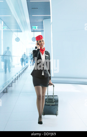 Young air hostess pulling luggage bag while on call in the airport - Stock Photo