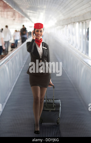 Young air hostess with luggage bag using cell phone while on call - Stock Photo