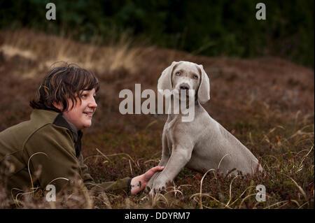 Huntress with Weimaraner puppy - Stock Photo