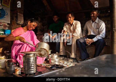 Indian female vendor pouring chai in cup with customers sitting at stall - Stock Photo