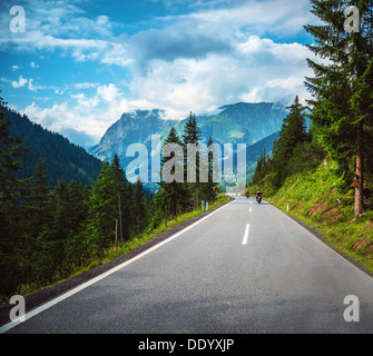 Group of bikers riding on road pass along Alpine mountains, travelers in Europe, mountainous highway, pine tree - Stock Photo
