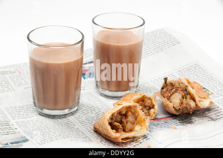 Indian chai with samosas on newspaper isolated over white background - Stock Photo