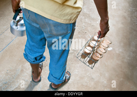 Rear view of Indian street seller with tray milk tea and kettle - Stock Photo