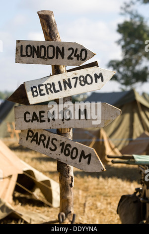 Sign posts on a branch directions to London Berlin Caen And Paris with Field Tents in background - Stock Photo