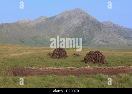 Stacks of peat (turf) in the Maumturk Mountains (County Galway) in the Connemara in Ireland - Stock Photo