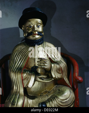 Gilt statue of Marco Polo holding a pomegranate, symbol of wealth and prosperity. Artist: Werner Forman - Stock Photo