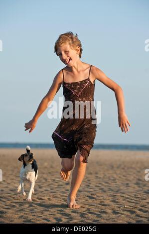 Girl running with a Dansk-Svensk Gardshund or Danish-Swedish Farmdog on the beach - Stock Photo