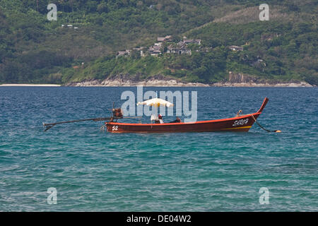 Longtail boat in the bay off Tri Trang Beach, Phuket, Thailand, Asia - Stock Photo