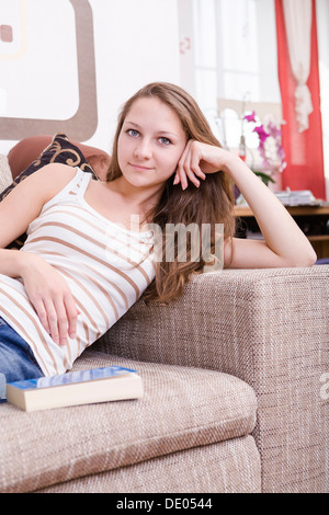 Girl sitting on sofa, a book next to her - Stock Photo