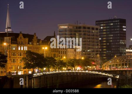Office buildings, St. Katharinen Church and Kibbelstegbruecke bridge on the Zollkanal canal in the evening, Hamburg - Stock Photo